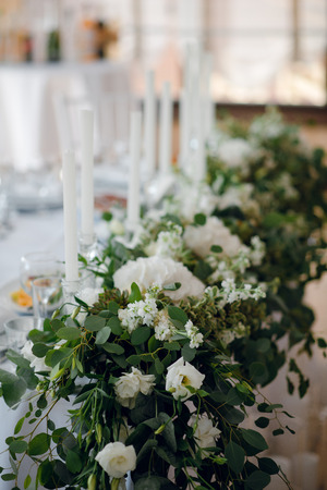 Close up wedding table decoration with the white flowers and greenery for the fiance and fiancee at the restaurant