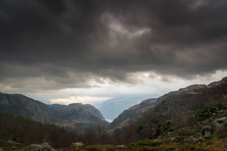 Dark stormy clouds above valley, forest and rocky mountains on background. Norway 写真素材