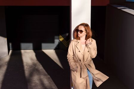Stylish red hair woman standing at the urban streets in long beige coat and sunglasses