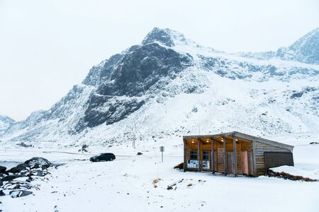 Wooden house with car against mountains covered in snow