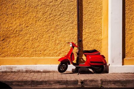 Red retro scooter is parked on old street in Rome. Summer sunny day