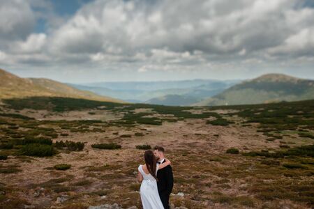Outdoor portrait of beautiful, sensual young couple of groom and bride in white wedding dress hugging in the needleleaf bushes in the mountains on sunny spring day