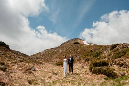 Portrait of young caucasian couple of groom and bride in white wedding dress holding hands while standing on a hill of beautiful mountains in spring
