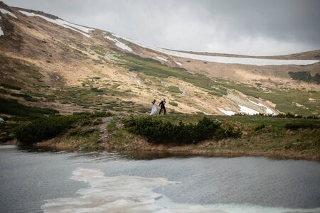 Scenic view of beautiful spring mountains and a lake. Wedding couple holding hands and walking on a hill. Beautiful landscape