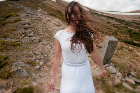 Portrait of sensual young woman in white lace dress standing on a wind on the hill in the mountains. Hair in the wind. Wedding concept Stock Photo