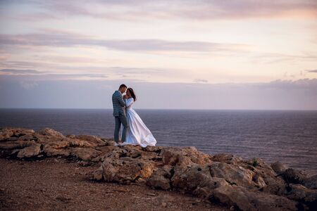 Gentle young wedding couple, bride and groom, walking and hugging on a rocky beach near the sea in evening Cyprus. Beautiful wedding photo shoot. Wedding for two, time for two. Archivio Fotografico