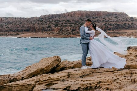 Romantic photo of newlyweds in love embracing on the background of the landscape of Cyprus sea and rocks. Wedding photo shoot, honeymoon of the newlyweds.