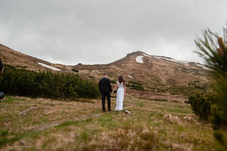Back view shot of young wedding couple of groom and bride holding hands while walking on the top of the hill in mountains