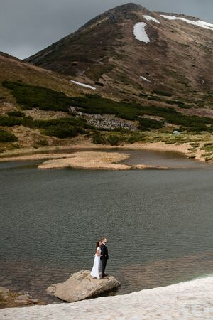 Wedding concept photo shoot. Beautiful young couple of groom and bride in white wedding dress standing on a big stone in a lake in spring mountains with snow