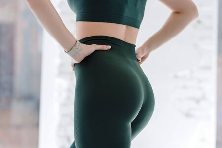 Cropped close up view photo of sporty sportive tempting beautiful attractive nice round wearing green tight pants leggings