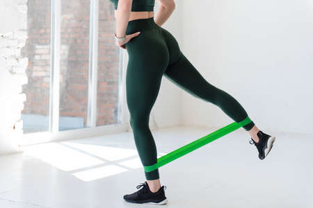 Close up of woman using rubber band for legs exercises