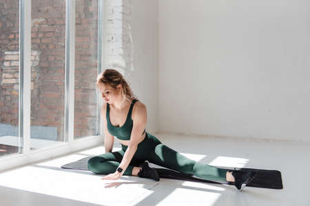 Healthy woman stretching legs after trainings on yoga mat 스톡 콘텐츠