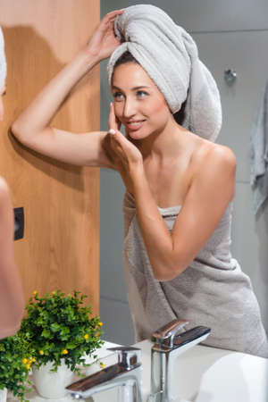 Woman wrapped in towel touching pretty face in bathroom