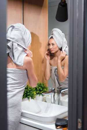 Happy woman in towel doing morning procedures after shower