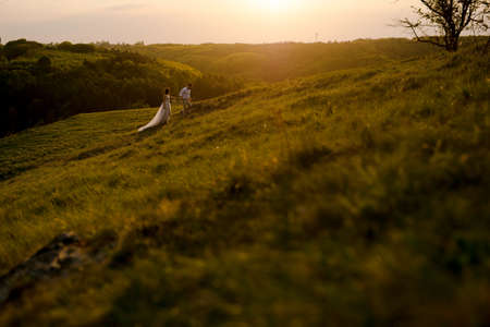 Scenic mountain view. Beautiful young wedding couple of groom and bride walking on the mountain hills on sunset.
