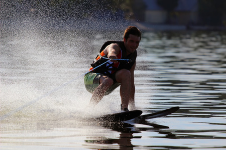 athlete touches the water when riding on water skis