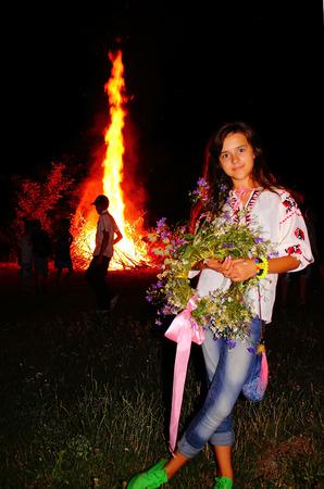 Meisje vieren St JPeople vieren jonsok rond een vreugdevuur in Oekraïne. St John's Eve feest rond een vreugdevuur doet denken aan midzomer heidense rituelen.