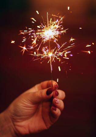 Women holding a burning sparkler firework in her hand.