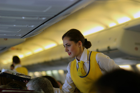 Beautiful flight attendant in an airplane smiling. Ukraine Editorial