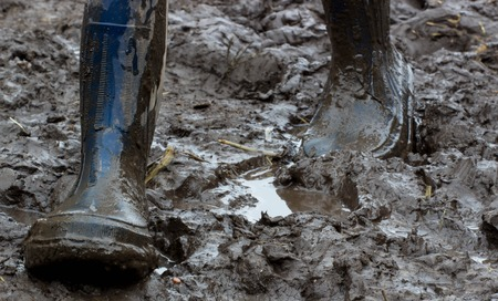 gait: Blue rubber boots covered in dirt. Gait in the mud . Ukraine