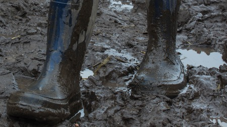 muddy clothes: Blue rubber boots covered in dirt. Gait in the mud . Ukraine