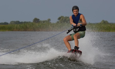 wakeboarding: athlete doing tricks on a wakeboard. Wakeboarding Stock Photo