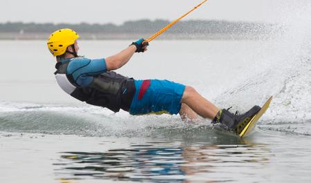 若い男は、ビーチの背後にあるウェイク ボードをジャンプします。
