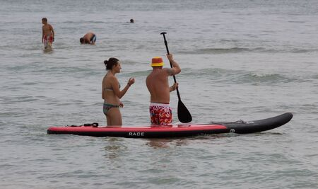 Lazurnoe , Ukraine, August 23, 2015: Festival of music and sports Crayzy Day , Two men paddle a kayak on the sea.