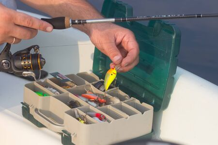 wobbler: Colorful Fishing Lures on plastic box  desk different fishing baits The fishing equipment. Man take wobbler Stock Photo