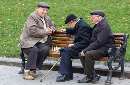 chess men: LVIV, UKRAINE - NOVEMBER 15, 2015:  old men are playing chess sitting on a bench in park of Lviv, Ukraine Editorial