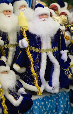 clauses: Toy band of merry Santa Clauses are in blue coats Stock Photo