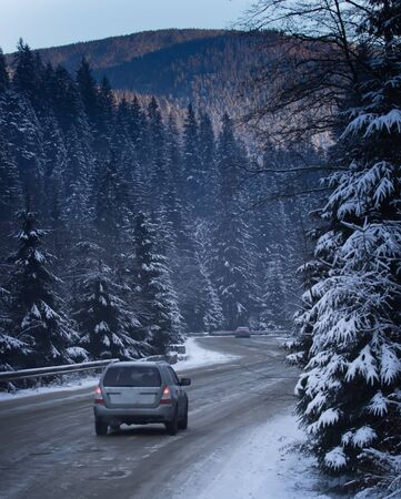 dangerous: Snowy road with traffic sign  Sudden and heavy snowfall on a country road. Driving on it becomes dangerous