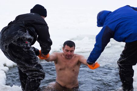 landscape background: Cherkassy, Ukraine - January 19, 2016: Experts rescuers Ministry of Emergency Situations rescues a boy pulling it from the ice-cold water Dnepr river