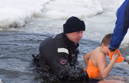 background image: Cherkassy, Ukraine - January 19, 2016: Experts rescuers Ministry of Emergency Situations rescues a boy pulling it from the ice-cold water Dnepr river