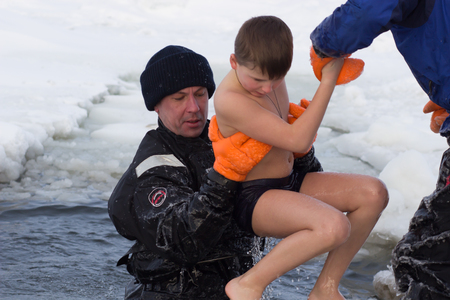 background colors: Cherkassy, Ukraine - January 19, 2016: Experts rescuers Ministry of Emergency Situations rescues a boy pulling it from the ice-cold water Dnepr river