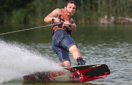 Male wakeboarder on pond in green park. Stock Photo