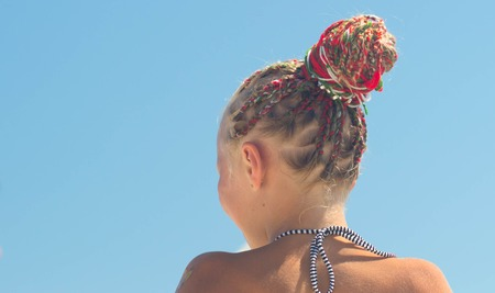 Hairstyle with many small plaited braids. Summertime outdoors close-up image.