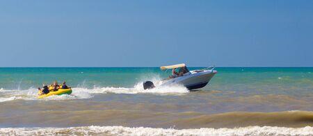 Auf einem aufblasbaren Schlauch auf dem Wasser fahren. Perfekte Sommerferien. Sommer Wassersport.