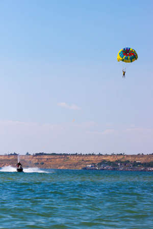 Parasailing in a blue sky near sea beach. Parasailing is a popular recreational activity among tourists i Stock Photo