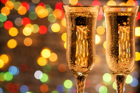 two glasses of champagne for the lovers in the new year. Dinner by candlelight with a beautiful bokeh Stock Photo