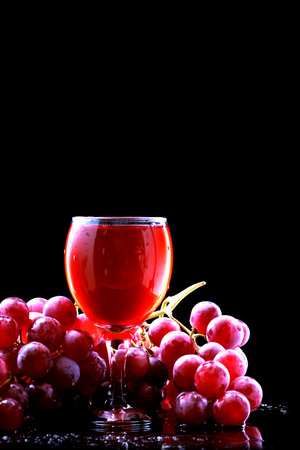 Wine glass and red grapes on a black background