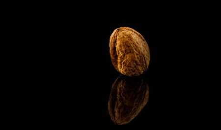 walnuts isolated on black reflective background. Stock Photo