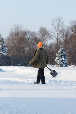 Man with snow shovel cleans sidewalks in winter. Winter time.