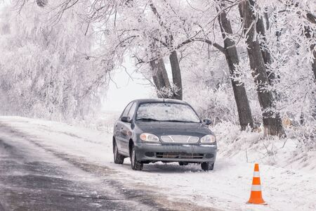 winter tires: warning triangle with winter car breakdown in background. Stock Photo