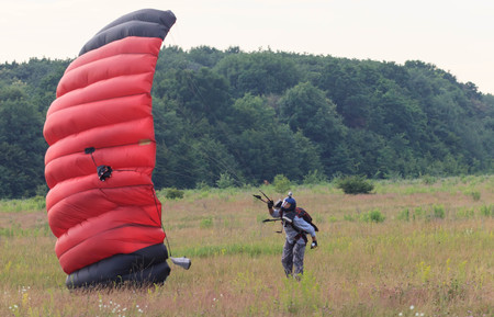 parachute jump: Sutiski, Ukraine - June 24, 2017: Skydivers carries a parachute after landing. Skydive Ukraine is the skydiving center located at Sutiski Aerodrome, about 20 km southwest of Vinitsa, Ukraine.