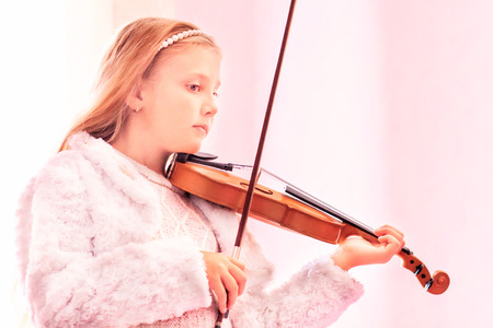 girl with long hair playing on violin