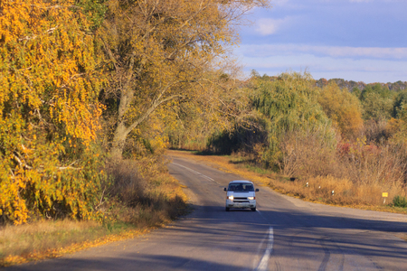 cars moving on a highway road in autumnal landscape Фото со стока