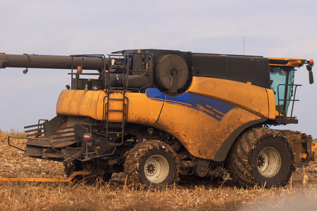Yellow modern combine harvester on stubble field at end of summer