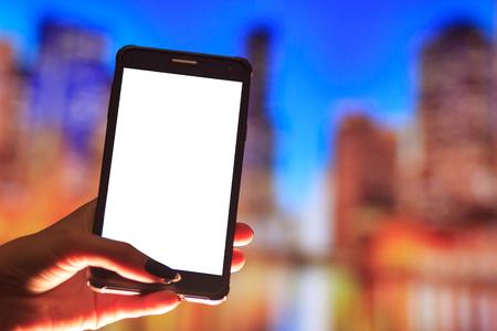 Женщина, используя свой мобильный телефон на улице, ночной свет Фото со стока