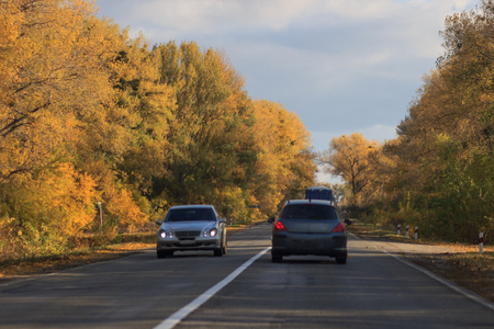 cars moving on a highway road in autumnal landscape Фото со стока - 90052930